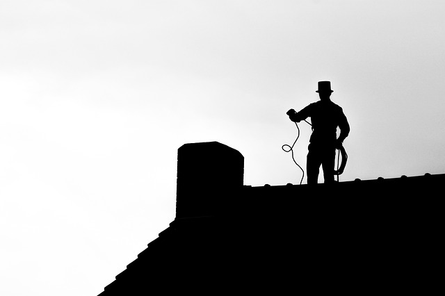 man som använder ett verktyg för att rensa en skorsten